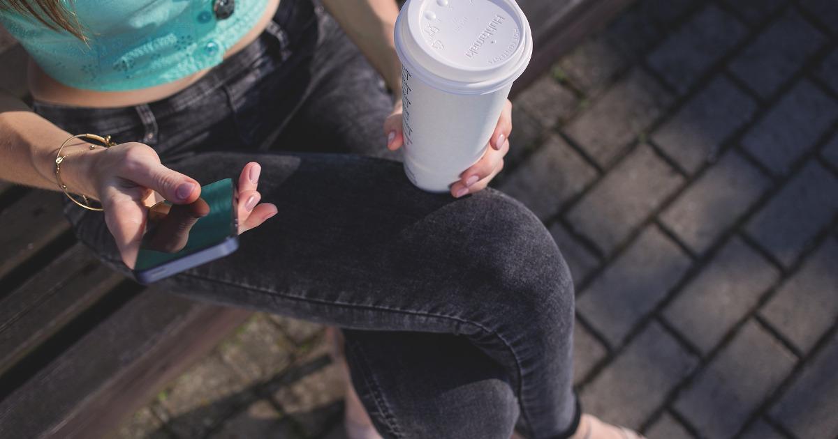 Девушка залипает в смартфоне и пьёт кофе
