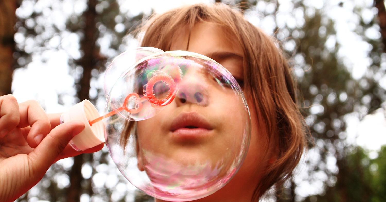 Ребёнок надувает мыльные пузыри