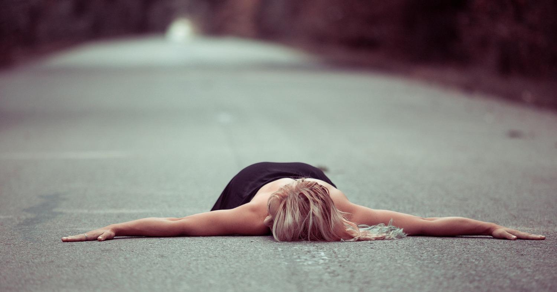 Девушка лежит на дороге