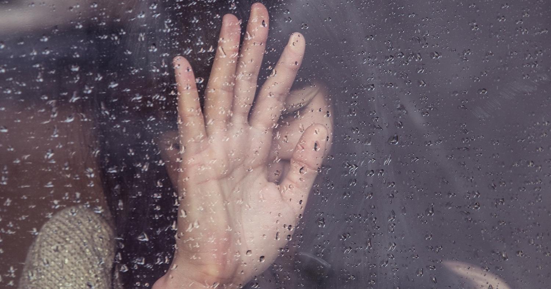 Грустная девушка плачет у окна