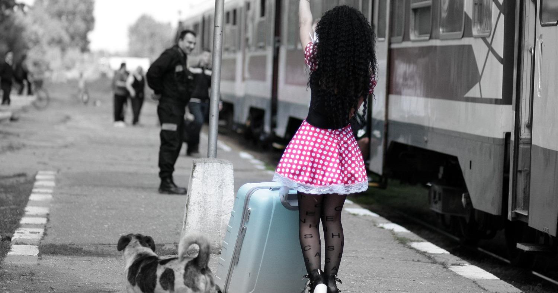 Красивая девушка в ярком платье возле поезда