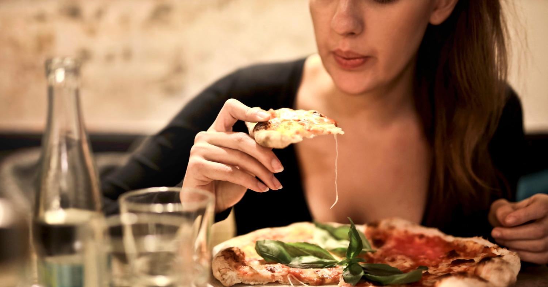 Женщина аппетитно кушает пиццу. Прямо кусает ломоть за ломтем. А-а-а-а... прямо пиццы хочется!