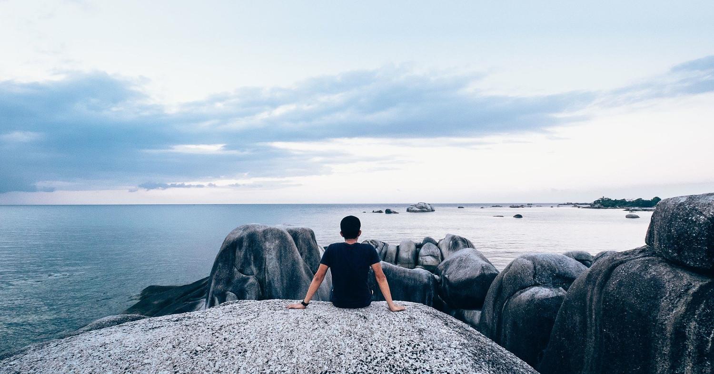 Мужчина сидит на берегу