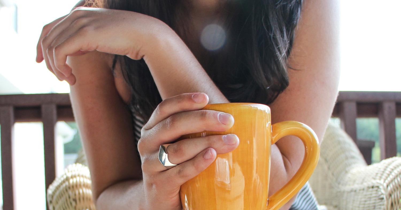 Девушка держит чашку с кофе